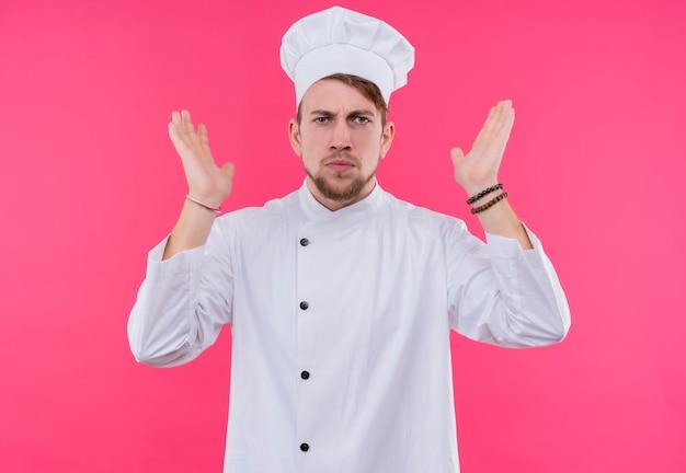 Een ontevreden jonge, bebaarde chef-kokmens in wit uniform die beide handen op een roze muur opheft