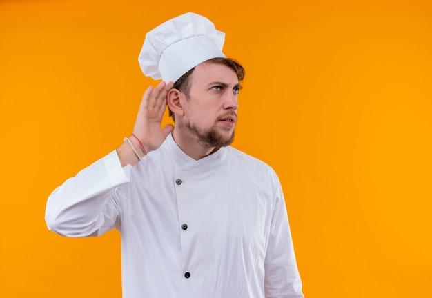 Een ontevreden jonge, bebaarde chef-kokmens in wit uniform die met hand over oor op een oranje muur probeert te horen