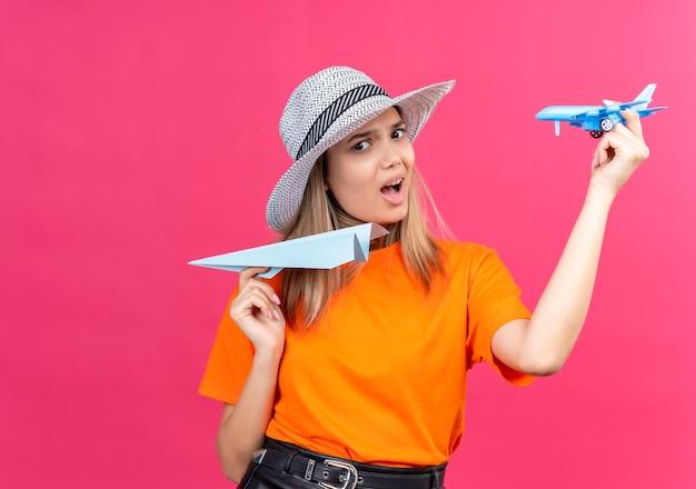 Een ontevreden, mooie jonge vrouw in een oranje t-shirt met een zonnehoed die een papieren vliegtuigje vliegt terwijl ze een blauw speelgoedvliegtuigje op een roze muur houdt