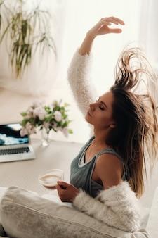 Een ontspannen meisje thuis drinkt koffie en kijkt naar een film. binnenlandse rust. het meisje zit comfortabel op de bank en drinkt koffie