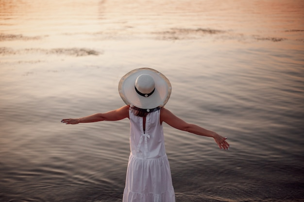 Een ontspannen vrouw geniet van de zon vrijheid en het leven op een prachtig strand bij zonsondergang het concept van vacati...