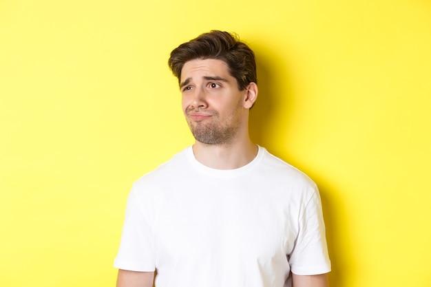 Een onwillige man in een wit t-shirt die naar links kijkt, sceptisch en ontevreden grijnzend, staande over een gele achtergrond
