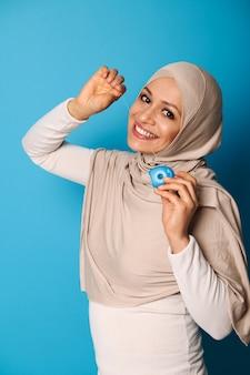 Een oosterse vrouw in een hijab glimlacht een brede glimlach naar de camera en gebruikt een tandzijde, poseren