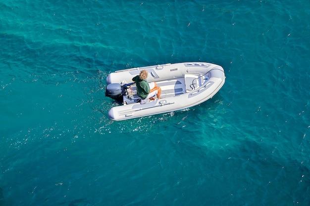 Een opblaasbare boot drijft langzaam met een motor op de azuurblauwe zee. boottocht op een zonnige zomerdag.