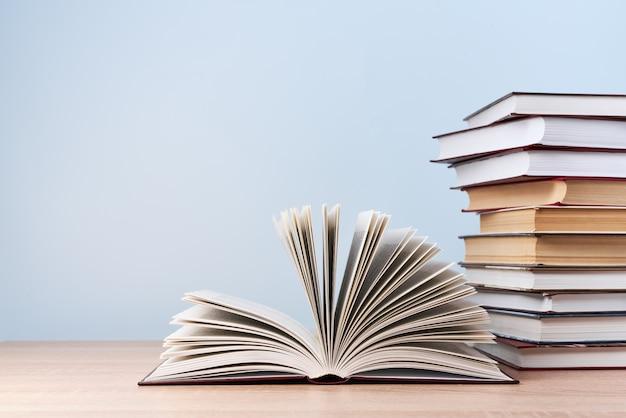 Een open boek en een stapel boeken bevinden zich op een houten tafel tegen een lichtblauwe muur