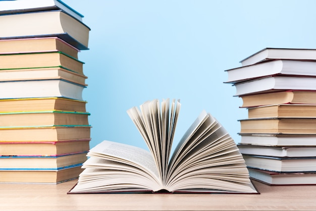 Een open boek en twee stapels boeken staan op een houten tafel tegen een lichtblauwe muur