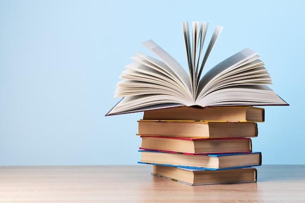 Een open boek ligt op een stapel boeken die op een houten tafel tegen een lichtblauwe muur staat