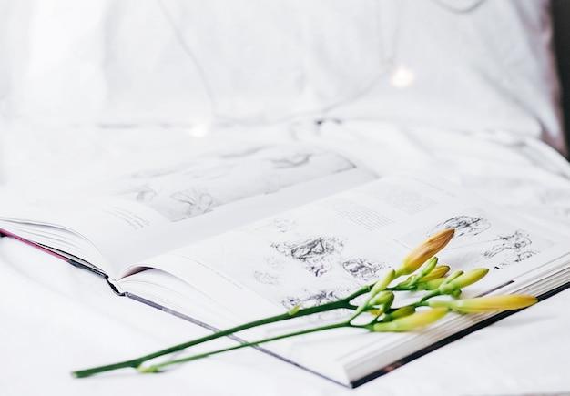 Een open boek ligt op het bed met een bloemlelie