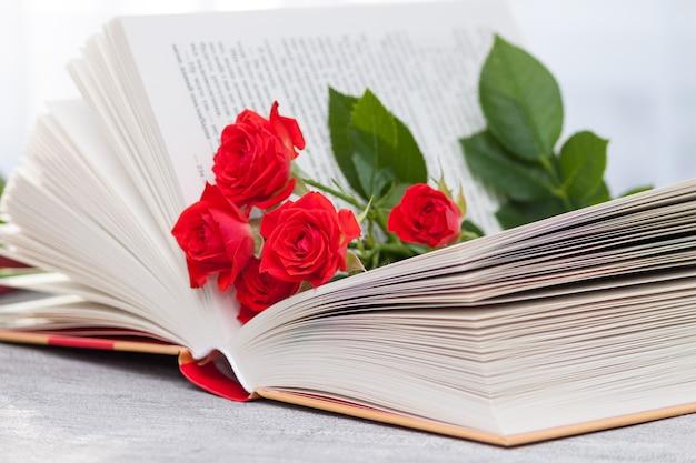 Een open boek met roodoranje rozen