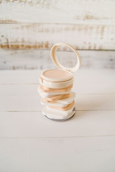 Een open compact poeder over de gestapelde spons op houten tafel