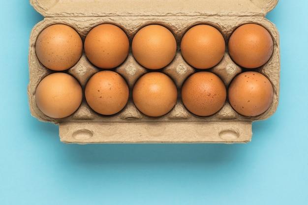 Een open doos eieren op een lichtblauwe achtergrond. een natuurproduct.
