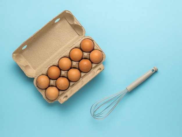 Een open doos met eieren en een garde om op een blauwe achtergrond te kloppen.