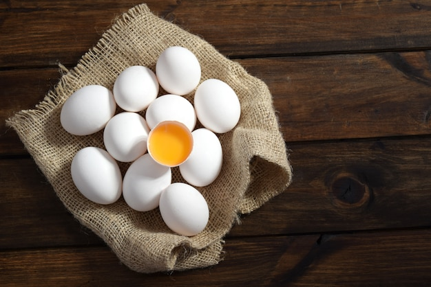 Een open ei boven op witte eieren op een zak in houten blackground