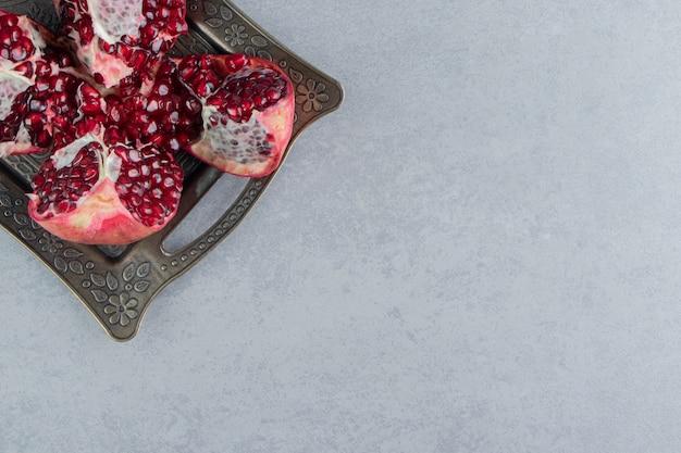 Een open granaatappel op een klein dienblad op marmer