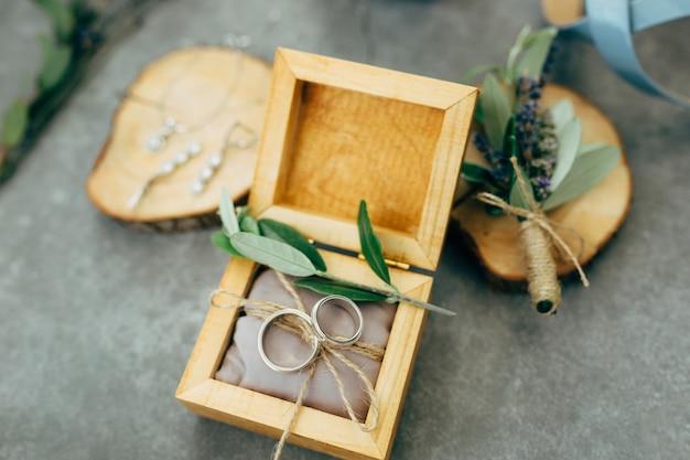 Een open houten kist met trouwringen en houten standaards met sieraden en een boeket bloemen