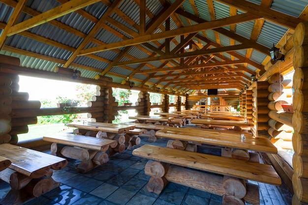 Een open houten veranda met veel houten tafels met banken.