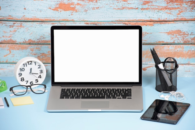 Een open laptop met een wit leeg scherm; digitale tablet en stationeries op blauwe bureau