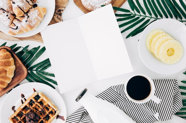 Een open lege kaart die met ontbijt op wit bureau wordt omringd