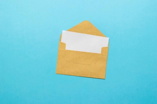 Een open post envelop met een ingesloten wit vel op een blauwe achtergrond. het concept van postcorrespondentie. plat leggen.