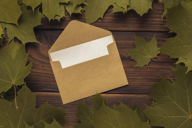Een open postenvelop met een vel papier in een frame van bladeren op een houten ondergrond. correspondentie.