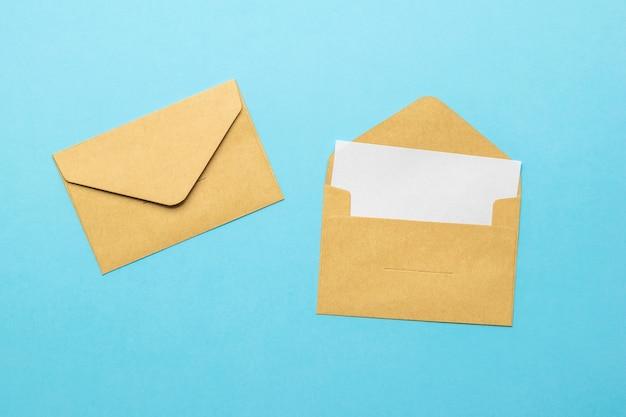 Een open postenvelop met een vel wit papier en een gesloten envelop op een blauwe achtergrond. plat leggen.