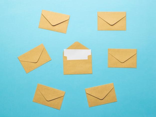 Een open postenvelop met een wit vel op een achtergrond van gesloten enveloppen op een blauwe achtergrond. plat leggen.