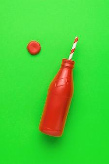 Een open rode fles en een cocktailbuis op een groene achtergrond.