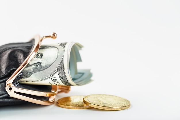 Een open zwarte portemonnee met geld, dollars en bitcoin munten op een witte muur.