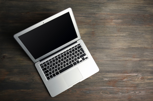 Een opengeklapte zilveren laptop op de houten tafel