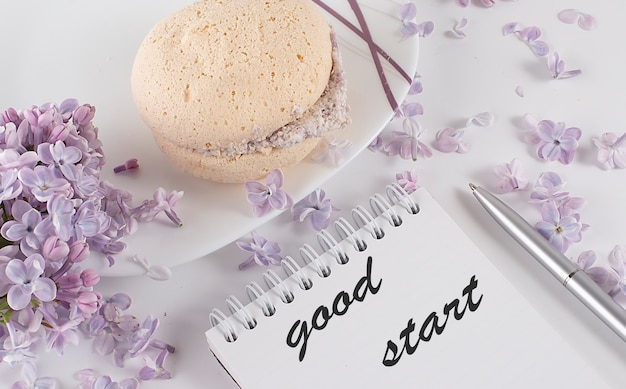 Een opengeslagen notitieboekje met en lila bloemen op een bureau en koekjes en tekst good start