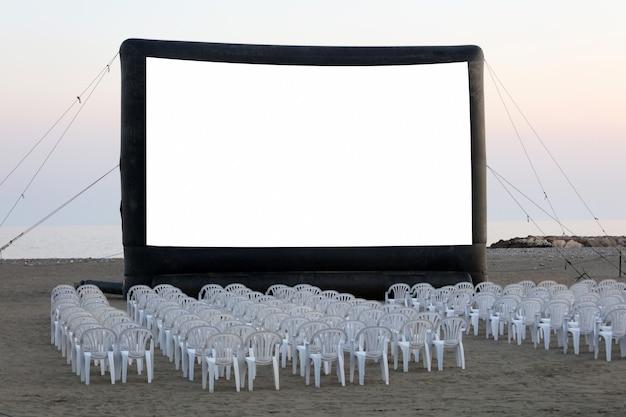 Een openluchtbioscoop op het strand bij zonsondergang met stoelen zonder mensen
