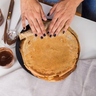 Een opgeheven beeld van de hand van de vrouw die de pannekoek rolt