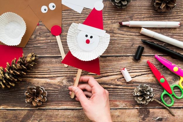 Een opgeheven mening van de hand die van de vrouwen de steun van de kerstman over de lijst houdt