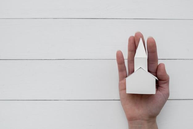 Een opgeheven mening van document huismodel op hand tegen houten achtergrond