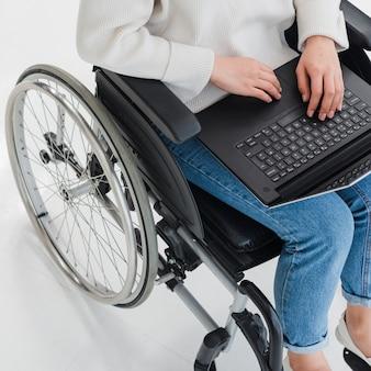 Een opgeheven mening van een vrouwenzitting op rolstoel die laptop met behulp van