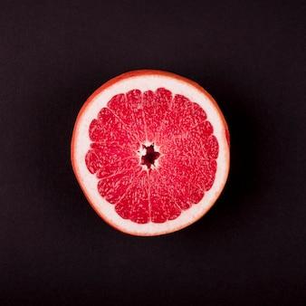 Een opgeheven mening van grapefruit dwarsdoorsnede tegen zwarte achtergrond
