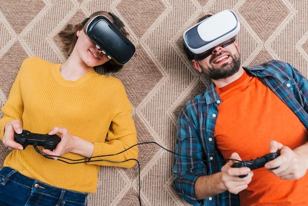 Een opgeheven mening van jong paar die op tapijt liggen die virtuele werkelijkheidscamera dragen die het videospelletje spelen