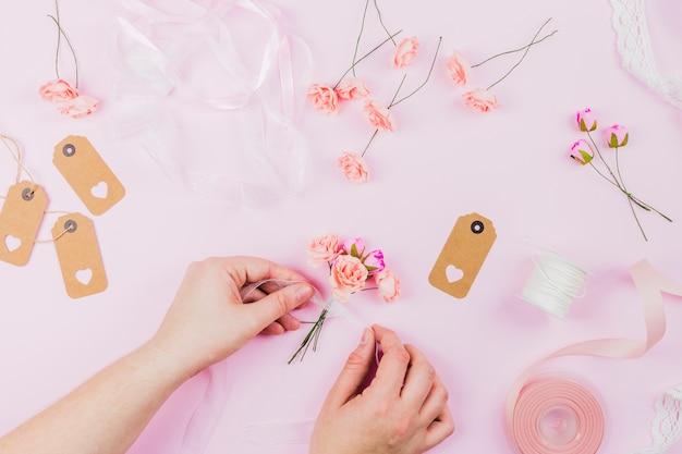 Een opgeheven mening van menselijke hand die de kunstbloemen met lint op roze achtergrond bindt