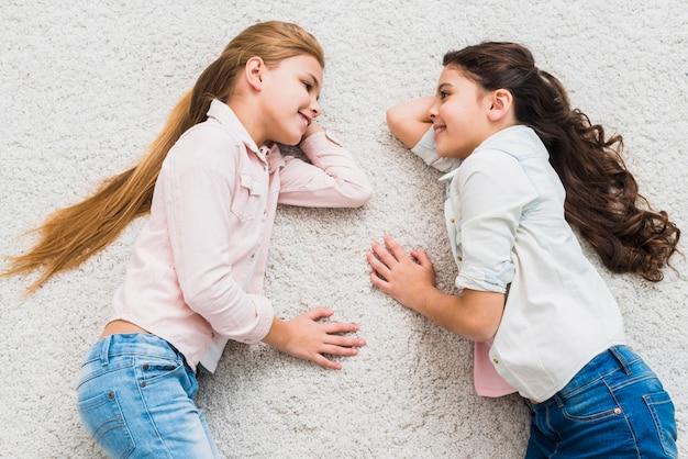 Een opgeheven mening van twee glimlachende meisjes die op tapijt liggen die elkaar bekijken