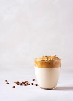 Een opgeklopte dalgona koffie in een glas op een grijze tafel