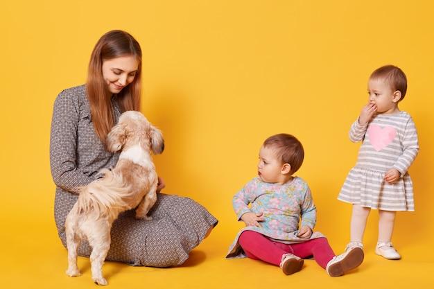 Een opgetogen gelukkige moeder speelt met haar favoriete huisdier, zittend op de vloer en ernaar kijkend