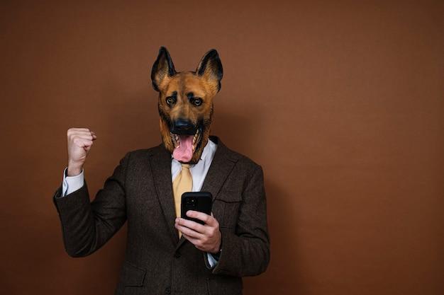 Een opgetogen man met smartphone en een latex hondenhoofdmasker dat zijn handen opheft