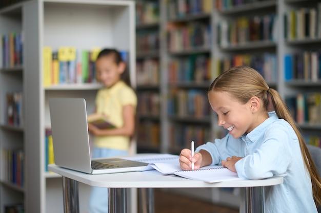 Een opgewekt blond schoolmeisje dat in haar notitieboekje schrijft en haar donkerharige vriendin bij een boekenplank