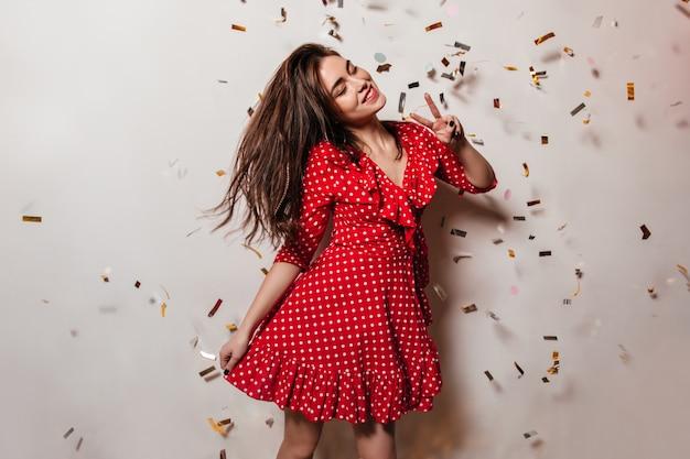 Een opgewekte jonge vrouw draagt een rode jurk met stippen. meisje met glimlach vormt op de muur van confetti en toont vredesteken.
