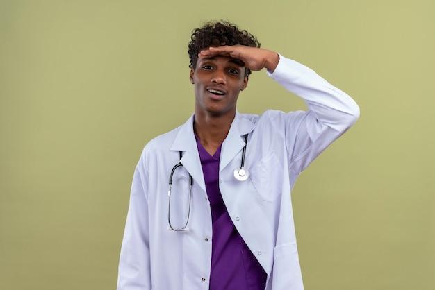 Een opgewonden jonge knappe donkere man met krullend haar in een witte jas met een stethoscoop die uitkijkt op een groene ruimte