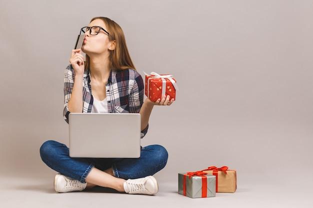 Een opgewonden toevallig meisje met laptopcomputer en creditcard zittend op een vloer met stapel geschenkdozen