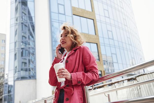 Een oproep ontvangen. volwassen mooie vrouw in warme rode jas wandelt in het weekend door de stad