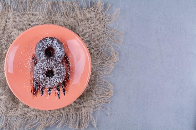 Een oranje bord heerlijke chocolade donuts met hagelslag op een jute