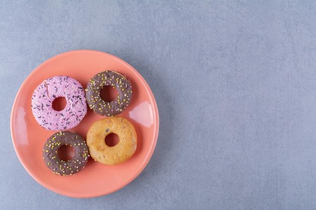 Een oranje bord heerlijke chocolade donuts met hagelslag.