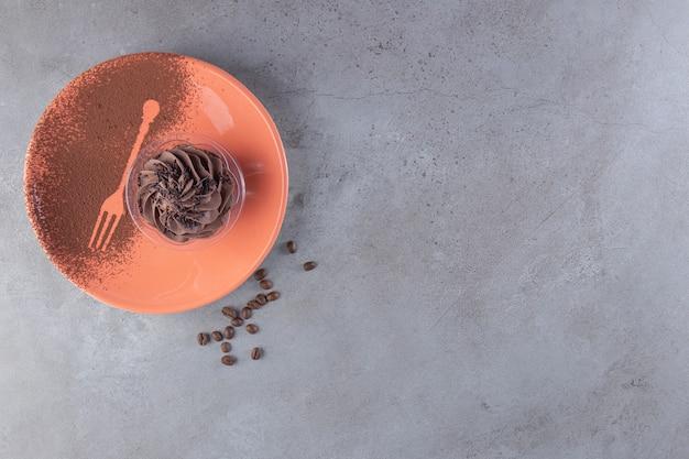 Een oranje bord met chocolade romige cupcake en koffiebonen.